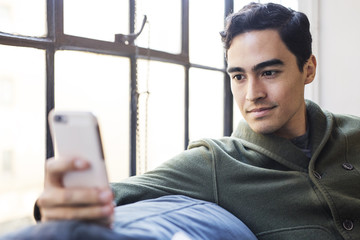 Businessman using phone while resting on sofa by window in office