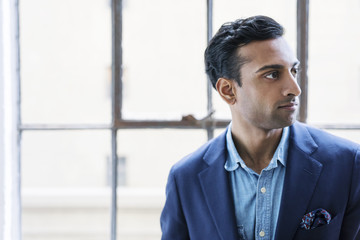 Thoughtful businessman sitting against windows in office