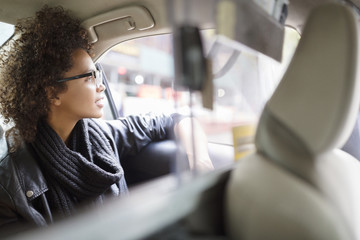 Woman looking through window while traveling in car