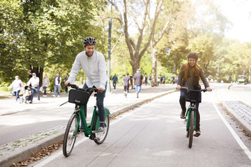 Happy couple riding bicycle in park