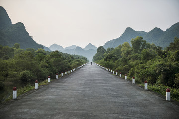 Empty road leading towards mountains against clear sky during foggy weather
