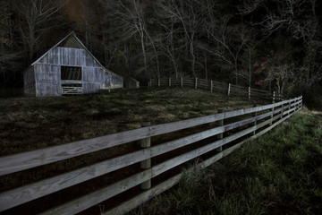 View of barn on field in forest at night