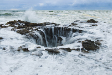 View of sea waves splashing on rock formations