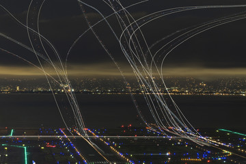 Light painting over illuminated airport by river in city at night