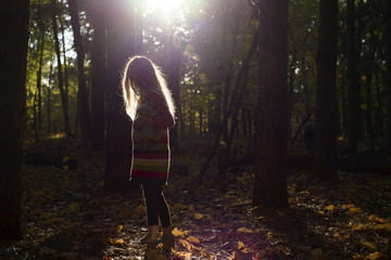 Side view of girl standing in forest
