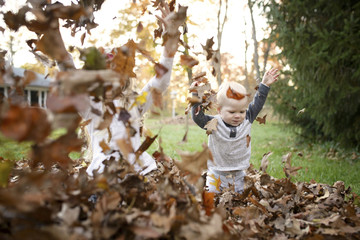 Cheerful siblings playing with dry leaves in backyard