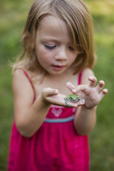 Girl playing with frog in yard