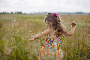Girl with arms outstretched playing on grassy field