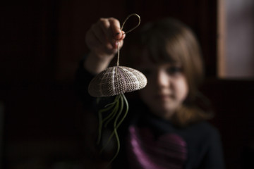 Girl playing with air plant hanging from sea urchin at home