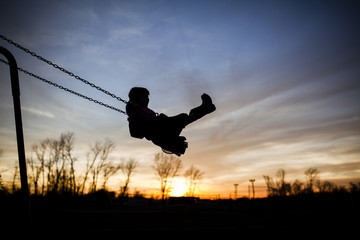 Silhouette girl playing on swing against sky during sunset