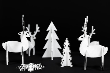 White Christmas decorations on a black background. Christmas reindeer and Christmas trees.