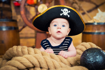 Newborn baby boy in a pirate hat is on the ropes. The interior of the ship's deck