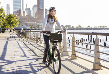 Happy woman cycling on bridge by river in city