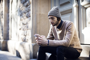 Man using mobile phone while sitting against house