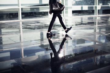 Low section of man carrying bag and walking in office
