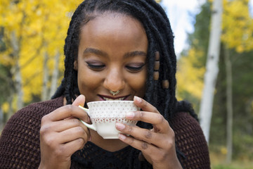 Happy woman drinking tea against trees in backyard