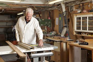 Carpenter measuring plank in workshop