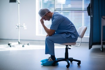 Tensed male nurse sitting in corridor