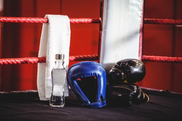 Boxing gloves, headgear, water bottle and a towel in boxing ring