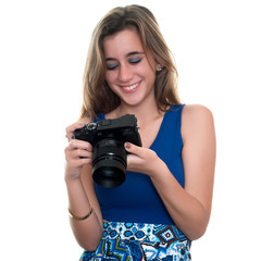 Pretty teenage girl looking at pictures on the rear display of a professional camera - Isolated on white
