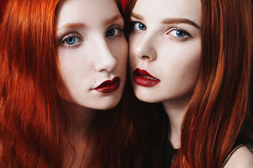Beauty Portrait Of Two Red Haired Girl On The Black And Red Background Two