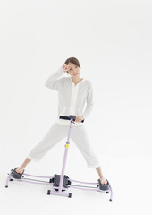 Young woman using leg machine