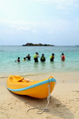 Yellow kayak on beach in evening day with blue sea background.