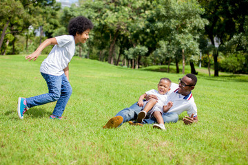 Two kids chasing and playing together while dad caught a boy in park