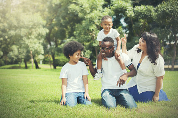 African American family alongside with Asian mum being playful and having good times in the park