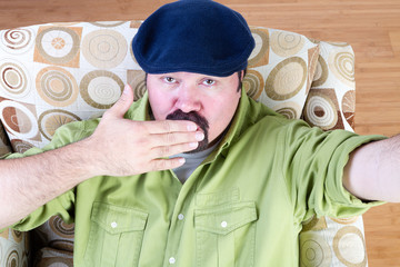 Overweight man in beret blowing kiss