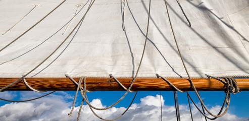 Sailboat canvas sail, horizontal wooden boom, rope rigging and sky. Close up
