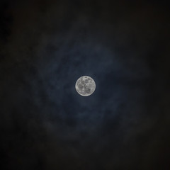 Full moon revealed by dark clouds at night.
