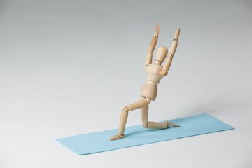 Wooden figurine exercising on exercise mat