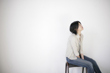 Young woman by white wall