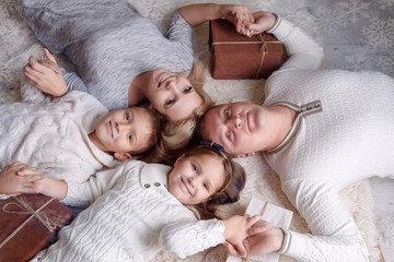 family with two children and giftboxes lying on the floor and lo