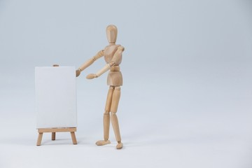 Wooden figurine standing next to white board
