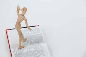 Wooden figurine standing on an open book