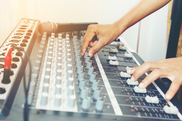Hand adjusting sound mixer control panel