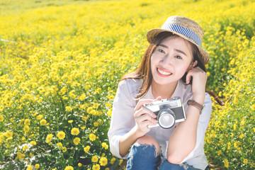 Asian hipster cute teen girl with camera in yellow flower garden