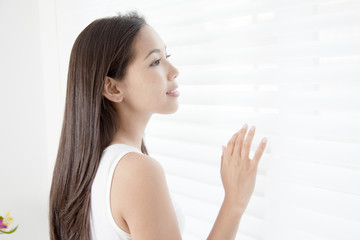 Young woman putting hand on blinds