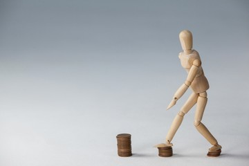 Wooden figurine stepping on stack of coins