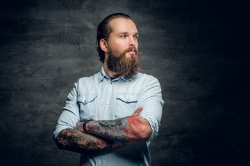 Portrait of bearded male with tattooed crossed arms.