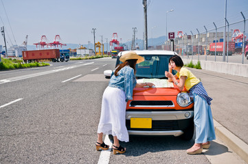 Two women spreading a map on the bonnet