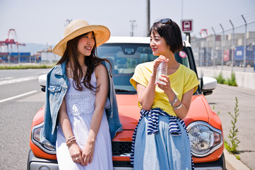 Two women talking in front of the car