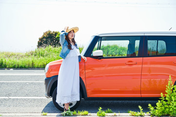 Woman standing and smiling in front of the car
