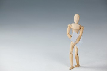 Wooden figurine standing and holding documents
