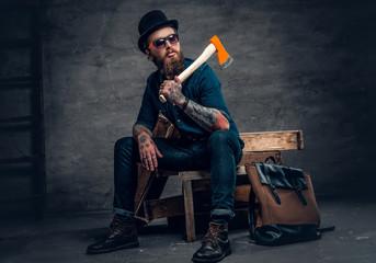 Tattooed bearded male holds an axe.