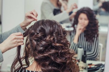 Close-up hairdresser coiffeur makes hairstyle in beauty salon. Barber at work