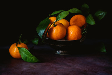 Still life of fresh tangerines with green leaves in vintage metal bowl. Toned image, low key technique (chiaroscuro). Close up view.