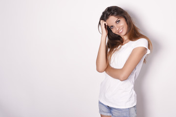 Young beautiful girl in a white T-shirt and denim shorts with a nice smile, smiling. Studio, white background, concept